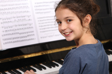 picture of a girl learning to play piano