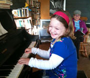 young girl enjoying a piano lesson